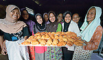 Women in Banda Aceh, on Indonesia's Sumatra Island, who lost their houses and belongings in the 2004 tsunami. The government provided them with a new house. Church World Service, a member of the ACT Alliance, helped the women form a cooperative and loaned them the money they needed to purchase new equipment and ingredients to restart their businesses, including baking pastries like they display here. The women repaid their loans to a revolving fund that they jointly manage.