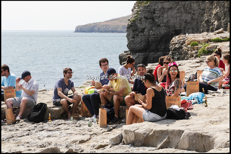 BNPS.co.uk (01202 558833)Pic: SaladCreative/BNPS<br /> <br /> 2018 Trip to the Jurassic Coast in Dorset.<br /> <br /> The generous boss treated her staff to a seaside trip last year too, where co-workers made the most of the weather and idlylic surroundings.<br /> <br /> A boss who took her 20 staff to Madrid for a Christmas party has now treated them a trip to the seaside to escape the hot office.<br /> <br /> Instead of being chained to their desks on a sunny day, thrilled workers donned swimwear and took turns diving into the sea before sitting down for a picnic.<br /> <br /> They rounded off the perfect working day with drinks in a local pub all paid by the company.