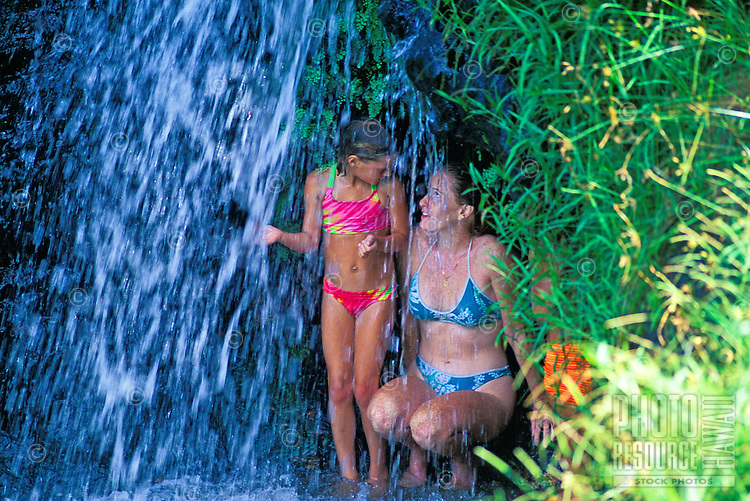 Mother and daughter under waterfall. Hanalei, Princeville, Kauai