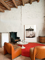 A pair of tan leather vintage chairs coupled with a high-backed black leather wing-backed armchair grouped around a retro, red circular rug