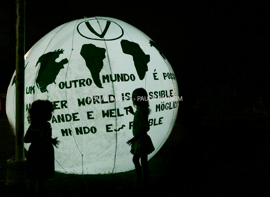 Two young girls playnng with globe of the world  during the World Social Forum on January 31, 2009 in Belem, Para, northern Brazil.