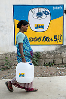 A woman carries a can of iJal water in Ambedkar Nagar in Medak, Telangana, India.