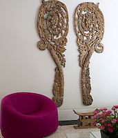 Two elaborately carved panels contrast with the simple, contemporary furnishings of the sitting room