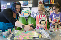NWA Democrat-Gazette/CHARLIE KAIJO Art instructor Mallory Gonzalez (left) blow torches the surface of a painting as Grace Cole, 7, of Fayetteville (center) and Aubrey Moses, 11, of Bentonville (right) watch during a Spring Break fluid art class, Monday, March 18, 2019 at iPaint in Rogers. <br />