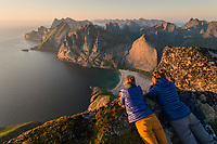 Two female hikers lie on edge of steep mounain peak above Bunes beach, Moskenesøy, Lofoten Islands, Norway
