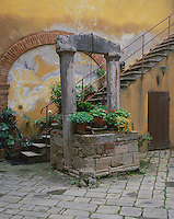 Tuscany, Italy:  Stone well and stairs with potted flowers in a courtyard in the hill town of San Quirico d'Orcia