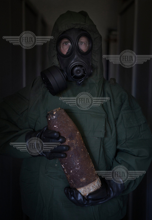 A member of the Belgian Unexploded ordanance diposal group , wearing his NBC suit, deals with a shell from WW1, suspected of being containing poison gas, Mustard of Phosgene. 24/4/13Copyright Photo Tom Pilston