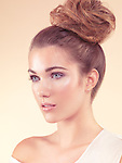 Beauty portrait of a young woman with natural look and hair in updo isolated on beige background