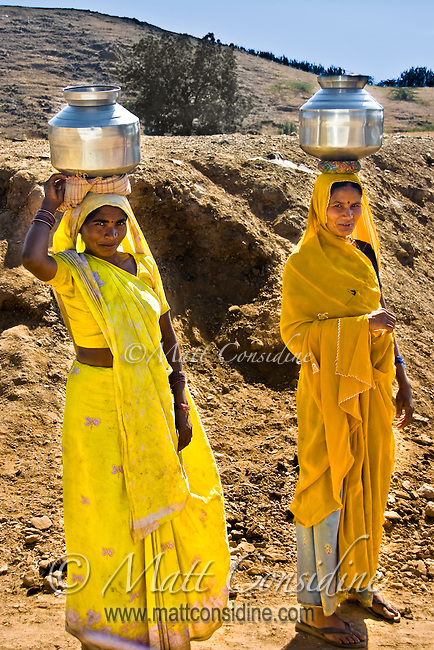 The saris of these women contrast starkly with the parched Rajasthani landscape.<br /> (Photo by Matt Considine - Images of Asia Collection)