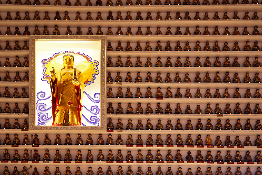 Hundreds of praying figurines on shelves on wall in main hall of the Ten Thousand Buddhas temple, Sha Tin, New Territories, Hong Kong SAR, People's Republic of China, Asia