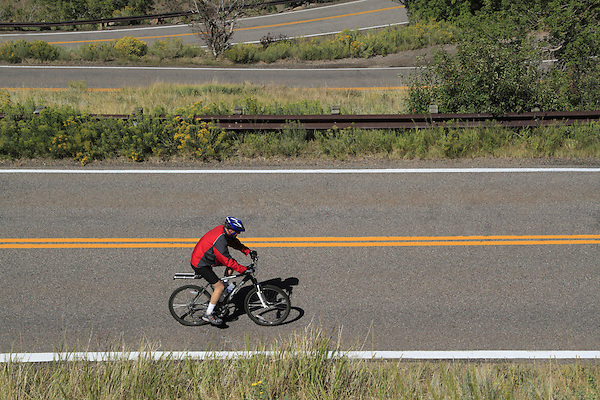 Older male biking uphill on Lookout Mountain Road west of Denver, Colorado. John leads private photo tours in Boulder and throughout Colorado. Year-round.