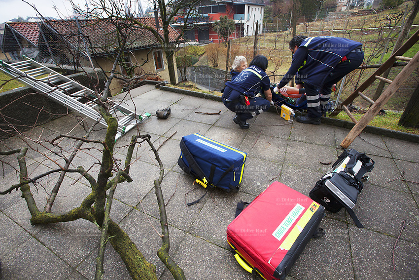 Switzerland. Canton Ticino. Comano. Paramedics team take care of an injured man during an emergency medical intervention. The man was cutting branches off a tree, fell on the ground and broke his right leg. He will be brought to hospital for medical surgery and recovery. Three paramedics wear blue uniforms and work for the Croce Verde Lugano. Both men (R) are professional certified nurses, the woman (C) is a volunteer specifically trained in emergency rescue. The Croce Verde Lugano is a private organization which ensure health safety by addressing different emergencies services and rescue services. Volunteering is generally considered an altruistic activity where an individual provides services for no financial or social gain to benefit another person, group or organization. Volunteering is also renowned for skill development and is often intended to promote goodness or to improve human quality of life. 27.01.2018 © 2018 Didier Ruef