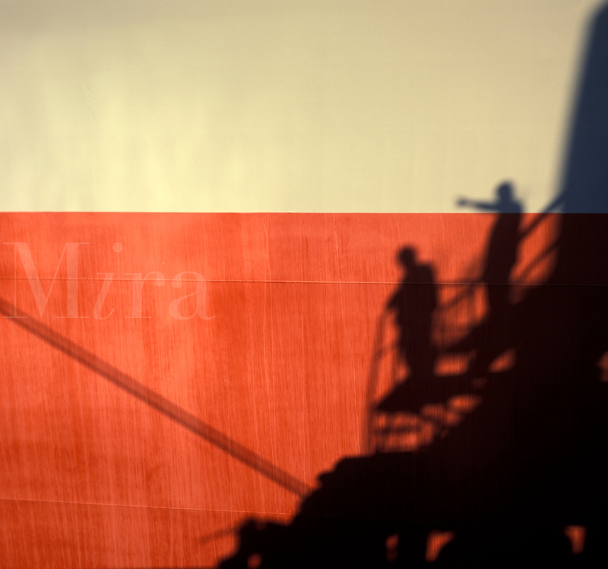 shadows of workers on ship hull