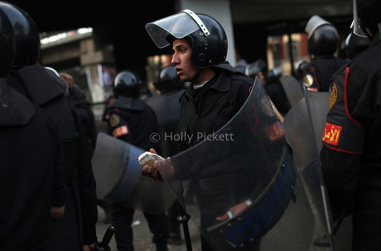 A policeman carries a rock in downtown Cairo, Egypt, Jan. 26, 2011. Violent clashes between demonstrators and police continued into a second day, as protesters attempted to build momentum in a movement inspired by the recent Tunisian uprising.
