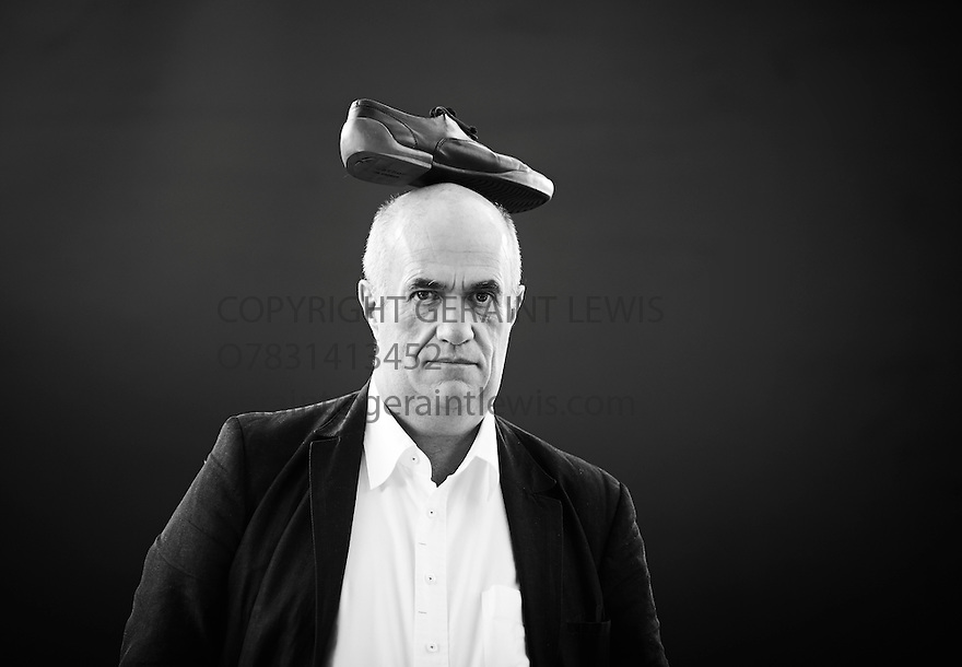 Colm Toibin, Poet and Writer, nominated for the Man Booker Long List 2013 with his shoe on his head  at The Edinburgh International Book  Festival 2013 . CREDIT Geraint Lewis