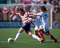 Abby Wambach (14) of the USWNT keeps the ball away from Mariam Ugalde (14) and Mariela Campos (7) of Costa Rica during a friendly match at Sahlen's Stadium in Rochester, NY.  The USWNT defeated Costa Rica, 8-0.