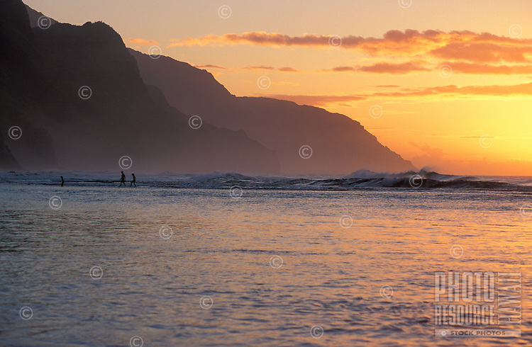 People walking in sandy shallows at sunset, Haena beach