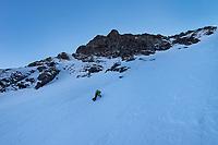 Female climber climbing steep snowy couloir on winter ascent of Mannen mountain peak, Moskenesøy, Lofoten Islands, Norway