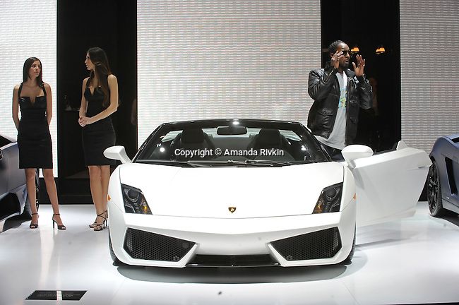 A man tries out a Lamborghini as two models stand nearby at the Lamborghini showroom at the Detroit Auto Show in Detroit, Michigan on January 12, 2009.