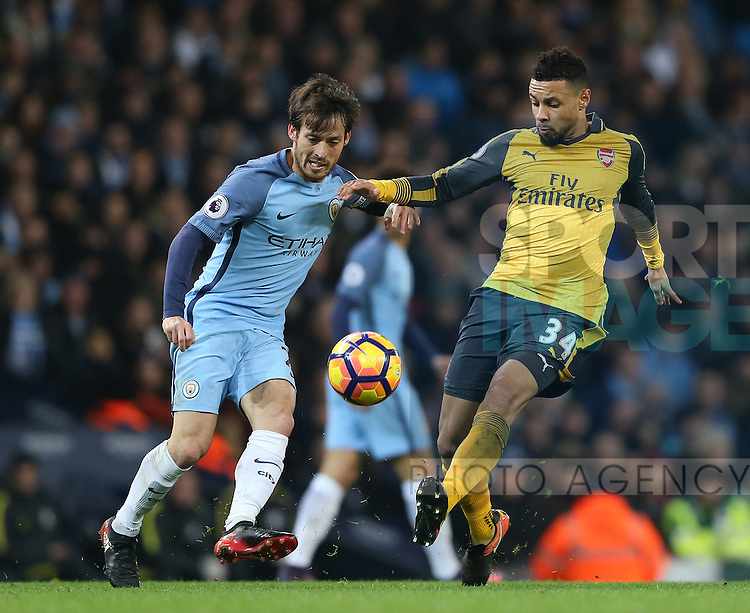 David Silva of Manchester City tussles with Francis Coquelin of Arsenal during the English Premier League match at the Etihad Stadium, Manchester. Picture date: December 18th, 2016. Picture credit should read: Simon Bellis/Sportimage