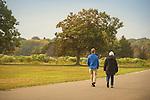 Hammonasset State Beach Park. Senior couple in jackets  walking on road.
