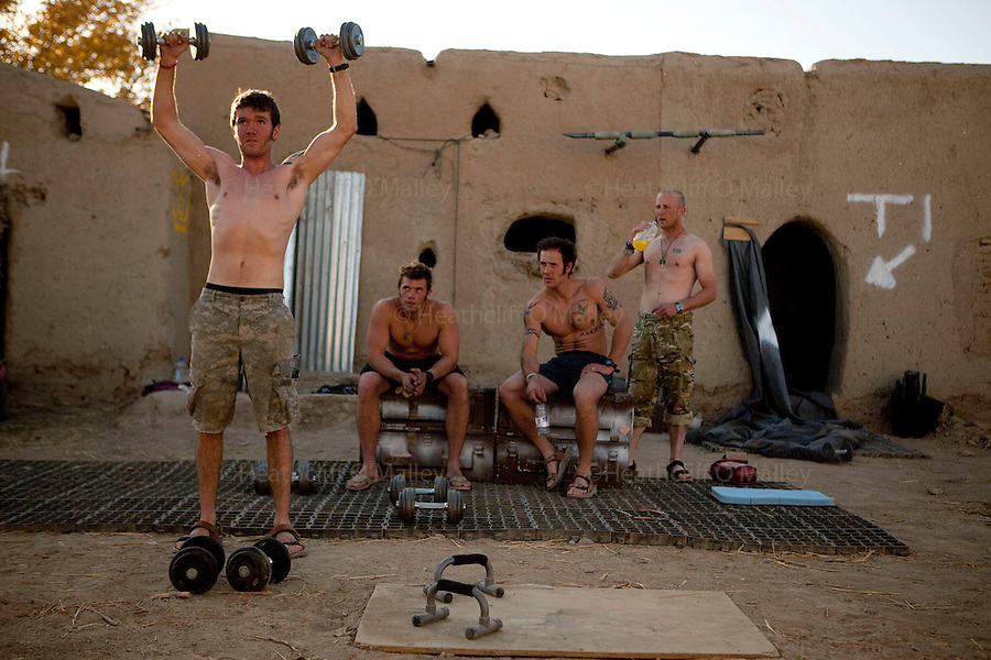 Mcc0027461 . Daily Telegraph..Pte Luke Flanagan works out whilst other men from his unit look on...photos showing life for the men at CP Qudrat from A Coy, 3 Para in the northern Nad e Ali district of Helmand Province...Helmand 6 December 2010