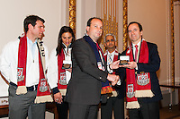 Stefhan Jekel, managing director of EMEA presents New York Red Bulls General Manager Jerome de Bontin with a present during the centennial celebration of U. S. Soccer at the New York Stock Exchange in New York, NY, on April 02, 2013.