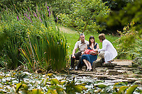 A mother breastfeeding her baby on the edge of a lily pond during a visit to Furzey Gardens in The New Forest  with her husband and mother.<br /> <br /> 10/07/2011<br /> Hampshire, England, UK