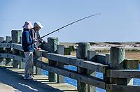 Mature couple fishing from bridge, Chappaquiddick, Massachusetts, USA.