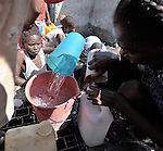 People scramble for water from a broken pipe in a Port-au-Prince neighborhood days after the January 12 earthquake that ravaged the Caribbean island nation.