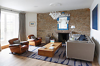 The contemporary living room has French windows which open onto a terrace overlooking the estuary
