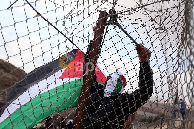 A Palestinian youth cut a section of Israel's separation fence in the West Bank village of Ramat near Ramallah to protest against Israel's military action on the Gaza Strip, on November 19, 2012 . Israeli air strikes across the Gaza Strip killed 13 people, raising the Palestinian death toll to 90 as Israel's relentless air campaign entered its sixth day. Photo by Issam Rimawi