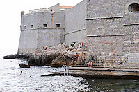 View of the Saint John's fort from the old harbour, people swimming in the sea Dubrovnik, old city. Dalmatian Coast, Croatia, Europe.