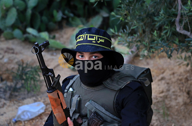A member of Palestinian militant form the Al-Quds Brigades, the armed wing of the Islamic Jihad movement guards the border between the Gaza Strip and Israel on the Muslim holy fasting month of Ramadan on June 17, 2017. Ramadan is sacred to Muslims because it is during that month that tradition says the Koran was revealed to the Prophet Mohammed. The fast is one of the five main religious obligations under Islam. More than 1.5 billion Muslims around the world will mark the month, during which believers abstain from eating, drinking, smoking and having sex from dawn until sunset. Photo by Dawod Abo Elkass
