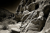 Sepia toned black and white image of a wooden ladder leading to a cavate in Bandelier National Monument in north-central New Mexico.