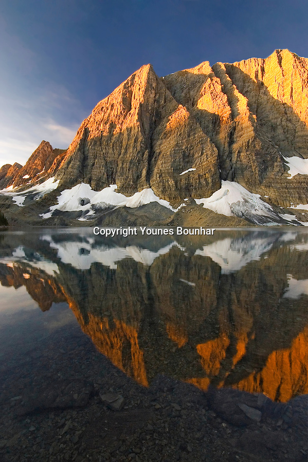 Alpenglow and perfect symmetrical reflection of the rockwall over Floe Lake glacial waters at sunrise