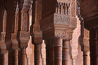 Slender columns with cubic capitals and arches above, carved with floral decoration and Arabic inscriptions, in the Court of the Lions, built 1362 in the second reign of Muhammad V, in the Nasrid dynasty Palace of the Lions, Alhambra Palace, Granada, Andalusia, Southern Spain. The design of the courtyard reflects the Nasrid view of Paradise, with these columns representing palm trees around a desert oasis. The Alhambra was begun in the 11th century as a castle, and in the 13th and 14th centuries served as the royal palace of the Nasrid sultans. The huge complex contains the Alcazaba, Nasrid palaces, gardens and Generalife. Picture by Manuel Cohen