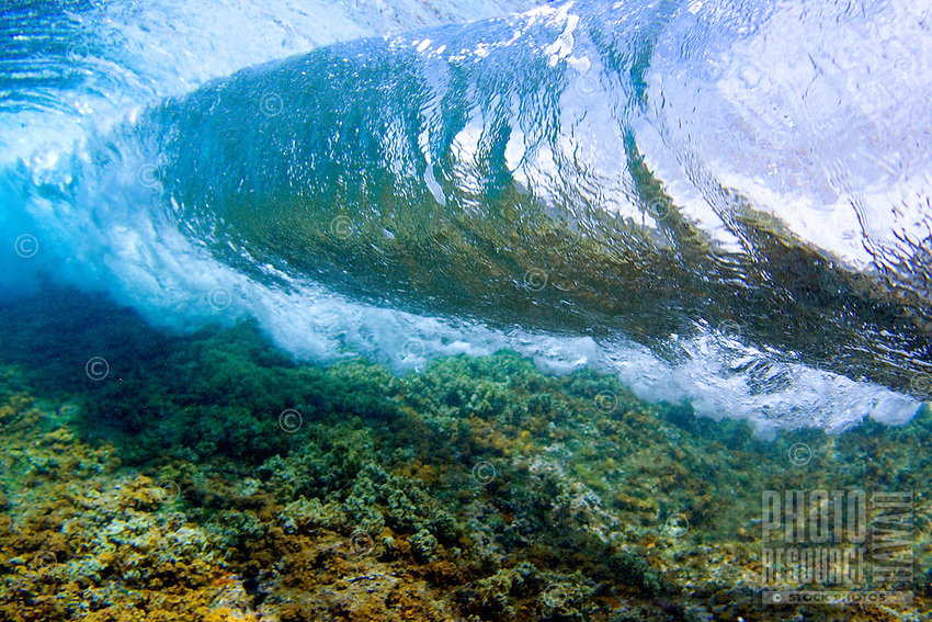 An underwater view of a breaking wave over a reef on O'ahu.