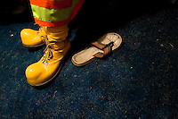 A Colombian man wears the yellow clown shoes before a performance at the Circo Anny, a family run circus wandering the Amazon region of Ecuador, 4 July 2010. The Circo Anny circus belongs to the old-fashioned traveling circuses with a usual mixture of acrobat, clown and comic acts. Due to the general loss of popularity caused by modern forms of entertainment such as movies, TV shows or internet, these small family enterprises balance on the edge of survival. Circuses were pushed away and now they have to set up their shows in more remote villages. The circus art and culture is slowly dying.