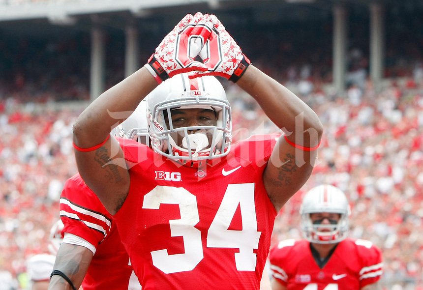 Ohio State Buckeyes running back Carlos Hyde (34) celebrates a touchdown run in the second quarter of the game against Miami on Sept. 1, 2012. (Dispatch photo by Adam Cairns)   Block O logo made by football gloves .