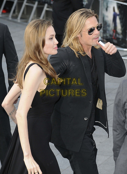 Angelina Jolie &amp; Brad Pitt<br /> 'World War Z' world premiere, Empire cinema, Leicester Square, London, England 2nd June 2013 <br /> half length black dress suit goatee facial hair couple sunglasses shades side profile <br /> CAP/CAN<br /> &copy;Can Nguyen/Capital Pictures