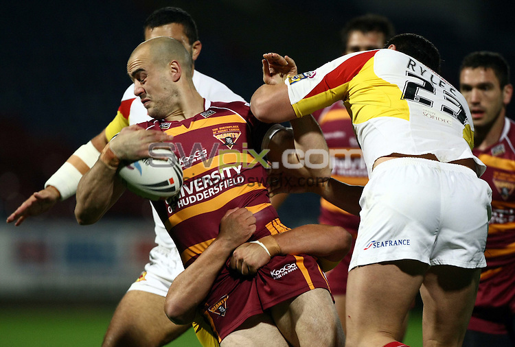 PICTURE BY VAUGHN RIDLEY/SWPIX.COM - Rugby League - Super League Playoffs - Huddersfield v Catalans - Galpharm Stadium, Huddersfield, England  - 25/09/09...Copyright - Simon Wilkinson - 07811267706...Huddersfield's Andy Raleigh is tackled by Catalans Jason Ryles and Greg Bird.