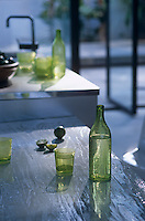 A selection of green glasses and bottles are scattered along the kitchen surfaces