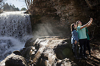 NWA Democrat-Gazette/CHARLIE KAIJO Melissa Wagner of Bella Vista and Shane Wagner of Santa Rosa, Fla. (from left), take a selfie in front of a waterfall, Saturday, January 5, 2019 at Tanyard Creek Nature Trail in Bella Vista.
