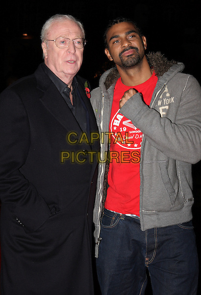SIR MICHAEL CAINE & DAVID HAYE.attending the European Premiere of 'Harry Brown' at the Odeon Leicester Square, London, England, UK,.November 10th 2009..half length black coat hand fist red t-shirt grey gray hoodie pose boxer glasses goatee facial hair in pocket .CAP/ROS.©Steve Ross/Capital Pictures.