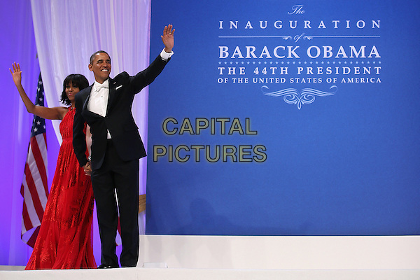 Michelle Obama & Barack Obama.2013 Inauguration Ball, Washinton D.C., USA..January 21st, 2013.full length black suit tuxedo red dress hand arm waving married husband wife        .CAP/ADM/CNP/CS.©Chip Somodevilla/CNP/AdMedia/Capital Pictures