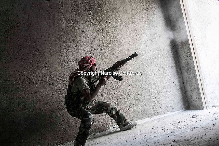 A rebel fighter belonging to the Kateba Omar Ben Abdul Aziz fires to the enemy position as he carries out a military operation to push back the Assad troops from the first line of fire in Aamria battlefield at the southwest of Aleppo City.