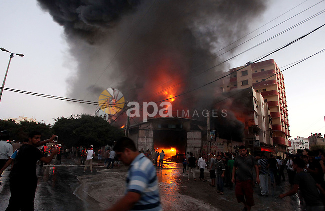 Palestinians look as firefighters try to extinguish fire from  soap factory that caught fire moments after it was hit by an Israeli airstrike in Gaza City August 10, 2014. Palestinian and Israeli negotiators on Sunday said they had accepted an Egyptian proposal for a new 72-hour truce with Israel, clearing the way for a possible resumption of talks on a long-term cease-fire arrangement in the Gaza Strip. Photo by Ashraf Amra