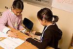 Education elementary Grade 3 science classroom two female students doing experiment with riulers and table edge horizontal