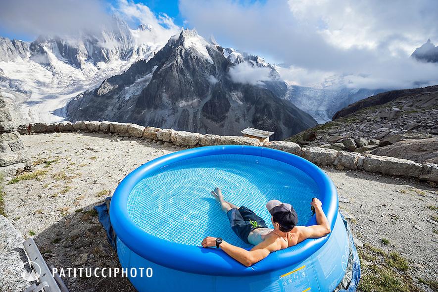 Outside the Couvercle Hut, a man humorously sits in a swimming pool and looks out at the Grandes Jorasses while drinking a beer. The summer of 2015 was so hot in the Alps that high temperature records were regularly set throughout Europe.